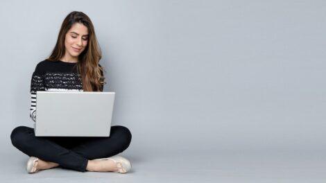 Hymyilevä, tummahiuksinen nainen istuu risti-istunnassa valkoinen kannettava tietokone avoimena sylissään.
