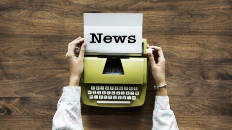 Kirjoituskone pöydällä ja kädet. Paperissa lukee News.